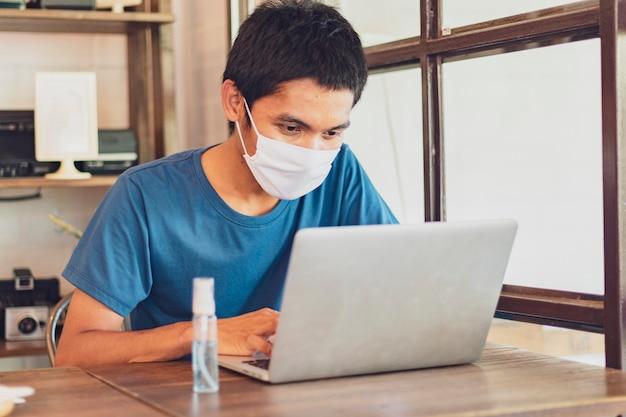 男性はコロナウイルスcovid-19から保護するためにマスクを着用し、自宅で仕事をしています