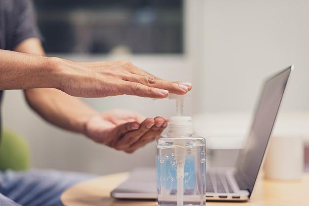 消毒ジェル、アルコールジェルを使用して、自宅の仕事机の上で手を消毒する手のクローズアップ。流行と社会的距離の期間中の予防策。 covid 19、コロナウイルス