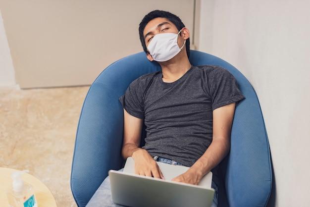 Covid-19、ラップトップコンピューターが付いているソファーで寝ているフェイスマスクを着ている男、コロナウイルスから保護するためにフェイスマスクを着ている、ビジネスレポート。在宅勤務。