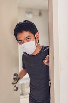 コロナウイルスまたはcovid-19。マスク保護を身に着けているアジア人の男性は、消毒ジェルで自宅で仕事をします。