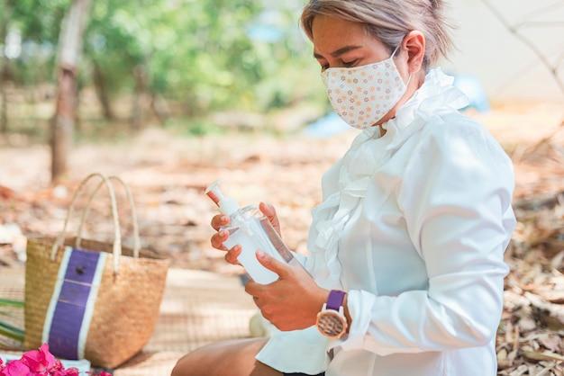 Covid-19は、女性がマスクを着用し、コロナウイルスに対してハンドジェルディスペンサーを洗います。