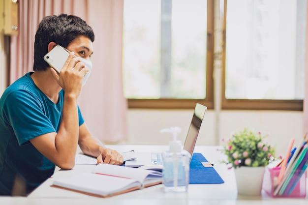 男はマスクを着用してコロナウイルスcovid-19から身を守り、自宅で仕事をします。