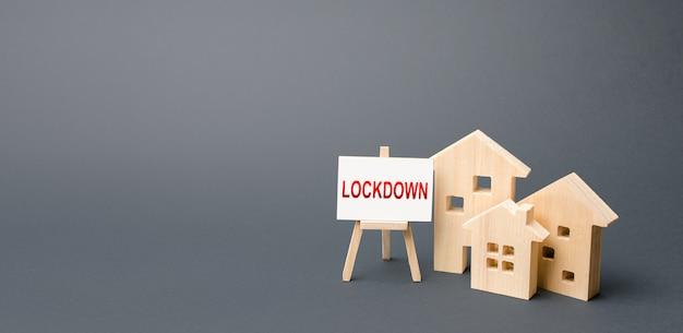 ロックダウンという言葉が付いた家とイーゼルの図。コロナウイルスcovid-19を阻止するための厳しい対策
