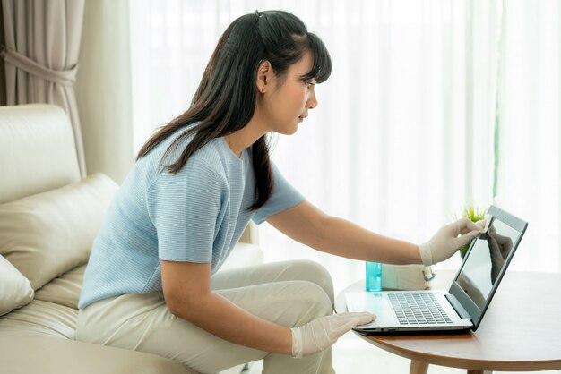 アジアの女性はアルコール、ラップトップコンピューターに消毒スプレーを噴霧し、covid-19ウイルスの感染を防ぎます