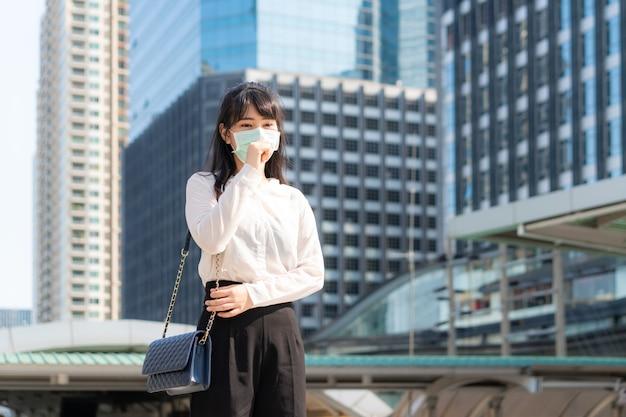 タイのバンコクにある事業所ビルで、咳をして気分が悪くなり仕事に行く白いシャツの若いアジア女性実業家が防塵マスクと防塵マスクcovid-19を着用しています。