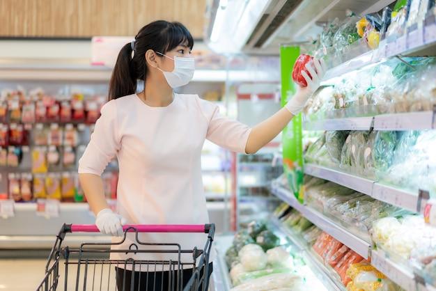 衛生的なマスクと食料品のショッピングカートにゴム手袋をしていて、パンデミック検疫の準備のためのcovid-19発生時に購入する新鮮な野菜パックを探しているアジアの女性