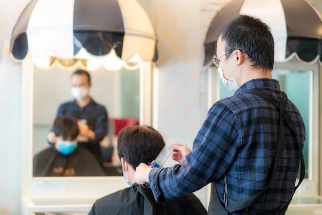 小説のコロナウイルス、理髪店ヘアケアサービスのcovid 19中に身を守るために医療マスクを身に着けているアジアの若い男と美容師の男。
