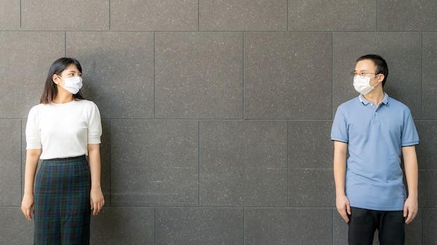 フェイスマスクを身に着けているアジアの若いカップルが屋外で壁に会い、壁に立って、感染のリスクと病気の予防のための社会的距離を隔てるcovid-19。