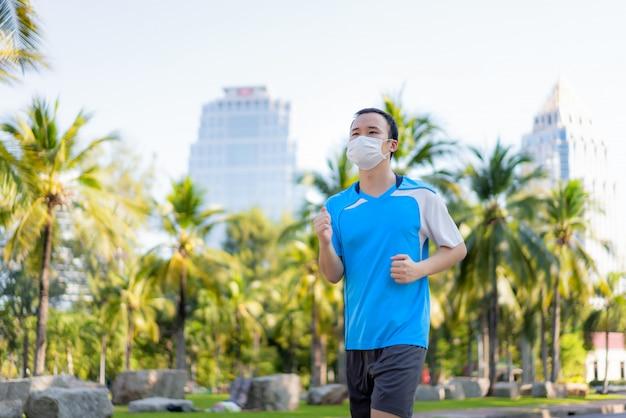 アジアの若い男がジョギングと屋外の都市公園で興奮し、タイのバンコクでのcovid-19パンデミックの間に健康のために保護マスクを顔につけています。