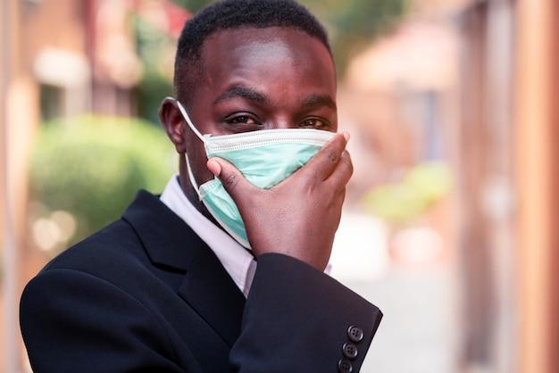 コロナウイルスまたはcovid-19から保護するための医療用マスクを持つアフリカの実業家