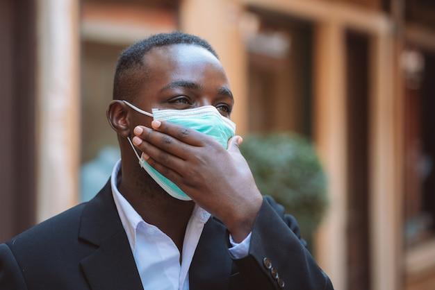 アフリカのビジネスマンはコロナウイルスまたはcovid-19から保護するための医療マスクを着用します