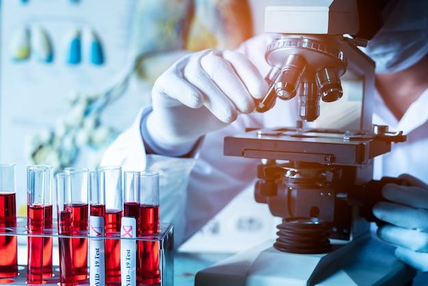 医療または医師がそれを探している研究室でテストサンプルを顕微鏡で調べるクローズアップ。コロナウイルスまたはcovid-19の概念