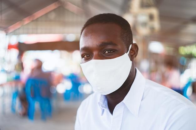 アフリカ人の男性が保護用コロナウイルスまたはcovid-19のフェイスマスクを着用