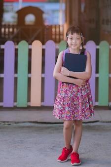 Covid-19検疫の後で学校に戻るときに顔のシールドを身に着けているアジアの小さな女の子の学生。