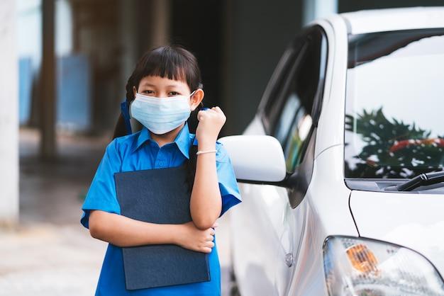 アジアの制服学生がコロナウイルスまたはcovid-19を保護するためにフェイスマスクを着用します。学校のコンセプトに戻る