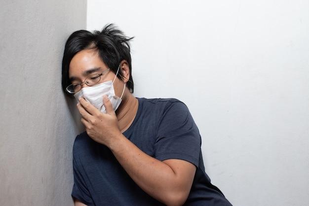 Мужской азиатский молодой человек нося хирургическую маску чувствуя больную головную боль и кашляя склонность на стене изолированной на белизне предохранение от вспышки коронавируса ухань (covid-19). концепция здравоохранения