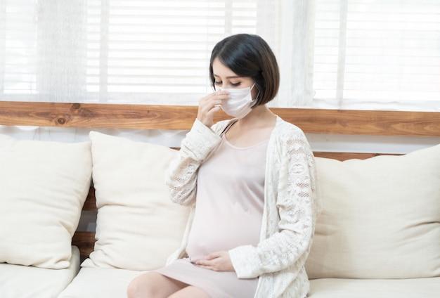 病気、めまい、パンデミック武漢コロナウイルス(covid-19)ヘルスケアの概念のために外科用医療マスクを身に着けているアジアの妊娠中の女性。