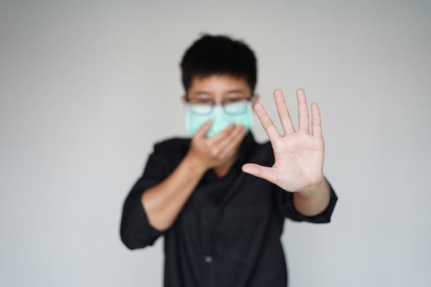 世界的なcovid-19ウイルスのパンデミックを予防するために顔の衛生マスクを着用している男性。彼の手を止めて顔のマスクをいっぱいにすると、感染性コロナウイルスの集団発生。