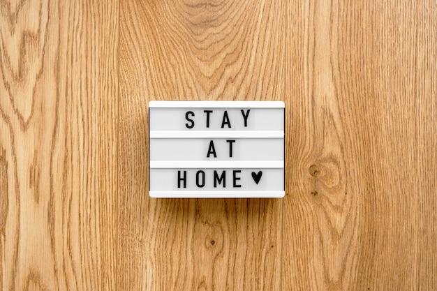 Лайтбокс с текстом пребывания дома на деревянной предпосылке. вид сверху плоская планировка covid-19 цитата