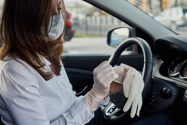 車を運転する防護マスクと薬の手袋の女性。コロナウイルスcovid-19感染から保護するための保護と自己分離