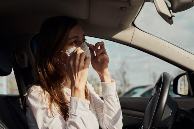 女性は車で運転する前に防護マスクを着用します。コロナウイルスcovid-19保護の概念