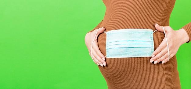 妊娠中の女の子の腹に医療マスクのバナー。保護を守ります。コロナウイルスの概念、covid-19、検疫