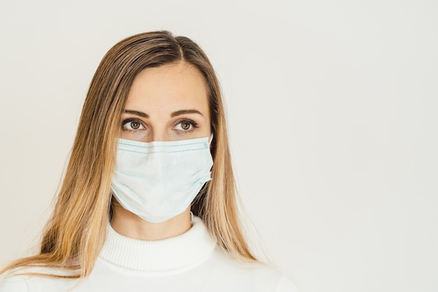 Covid-19の発生を心配しているフェイスマスクの気になる女性