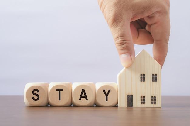 安全に家にいてください。木製のサイコロのメッセージ。コロナウイルスの大発生(covid 19)