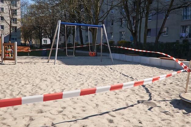 Пустая игровая площадка без детей, привязанная к детям и родителям. закрывается полосатой красно-белой барьерной лентой. ограничения, карантин для заболевания, вызванного новым коронавирусом covid-19.