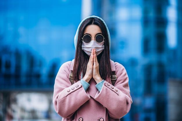 Женщина в медицинской маске молиться на открытом воздухе в пустой город. охрана здоровья и профилактика вирусных эпидемий, коронавирус, covid-19, эпидемия, пандемия, инфекционные заболевания, концепция карантина