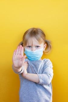 Маленькая кавказская девушка в маске против коронавируса covid-19