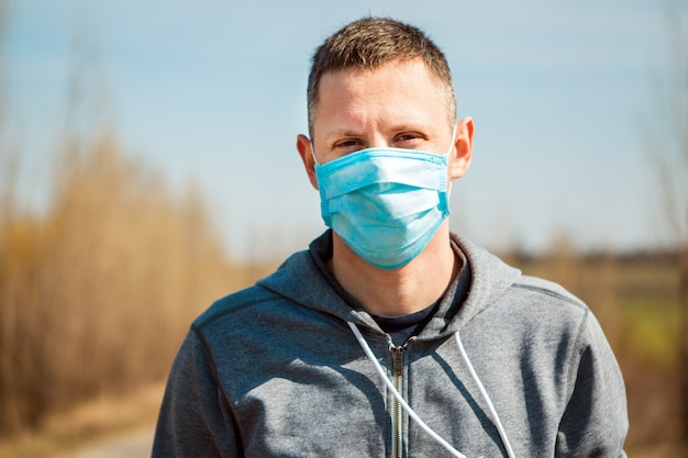 Covid-19男は彼の手の一時停止の標識を上げた。医療マスクの男。防護マスクの男