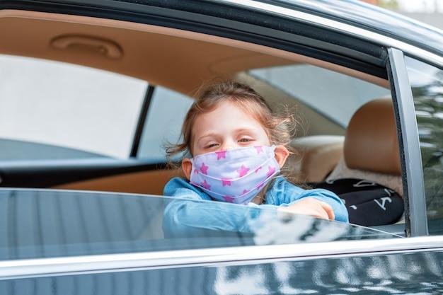 車の窓から医療マスクの少女。衛生マスク保護コロナウイルスまたはcovid-19
