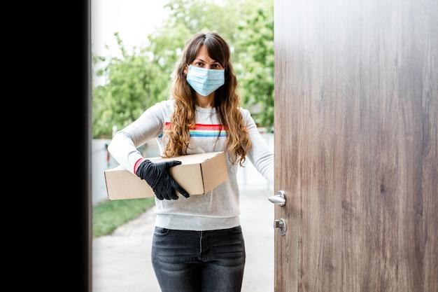Женщина-курьер доставляет посылку домой. женщина в медицинской маске. безопасная доставка covid-19