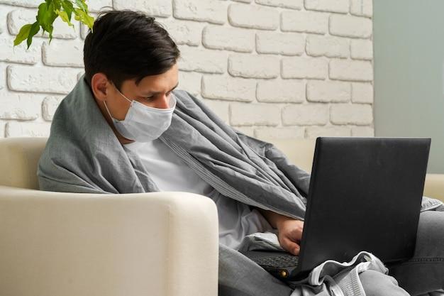 コロナウイルスの間に家にいる白人男性/医療用マスクを身に着けているcovid-19検疫