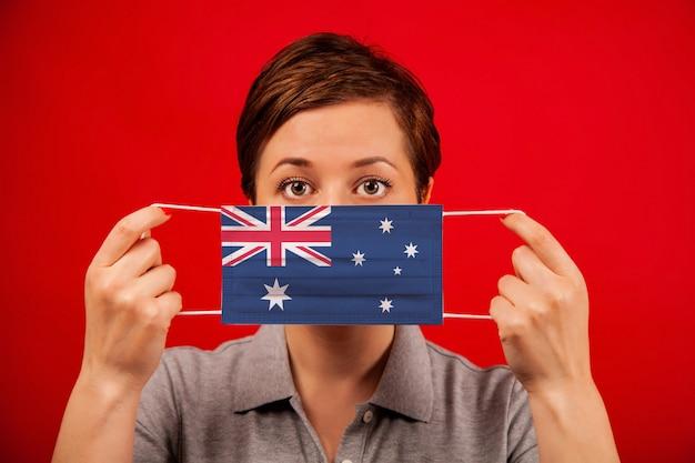 オーストラリアのコロナウイルスcovid-19。オーストラリアの旗のイメージを持つ医療防護マスクの女性。