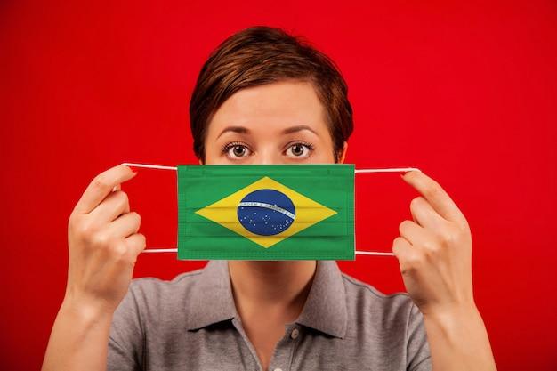 ブラジルのコロナウイルスcovid-19。ブラジルの国旗のイメージを持つ医療防護マスクの女性。