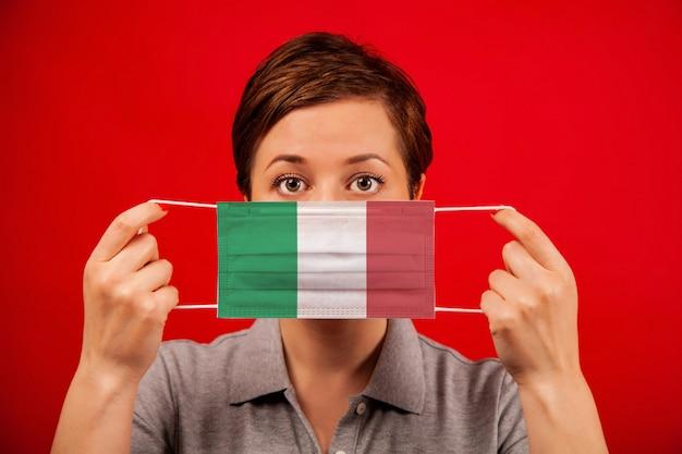 イタリアのコロナウイルスcovid-19。イタリアの旗のイメージを持つ医療防護マスクの女性。