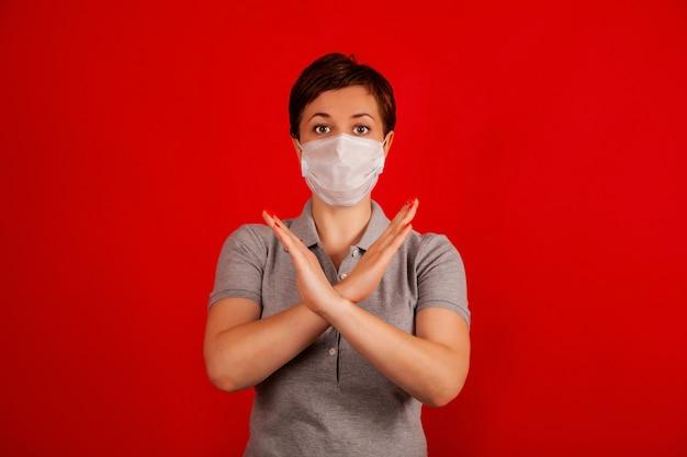 Женщина в маске указывает на прекращение распространения вируса covid-19. концепция предотвращения распространения эпидемии и лечения коронавируса.