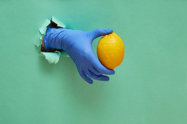 Концепция лечения коронавирусом или covid-19. рука в синей защитной резиновой перчатке держит лимон. современная тенденция отверстие в бумаге с копией пространства.