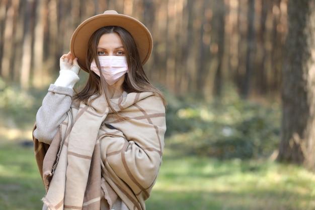 Молодая стильная женщина в медицинской защитной маске от covid-19, коронавирус на открытом воздухе.