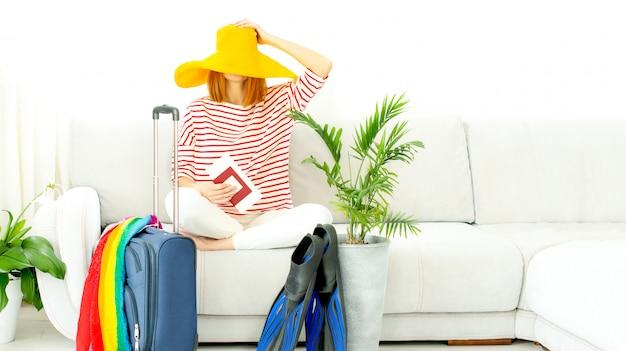 Женщина в желтой шляпе сидит дома и планирует поездку на отдых. чемодан и ласты для дайвинга. закрытие границ и запрет на полеты из-за карантина и covid-19.
