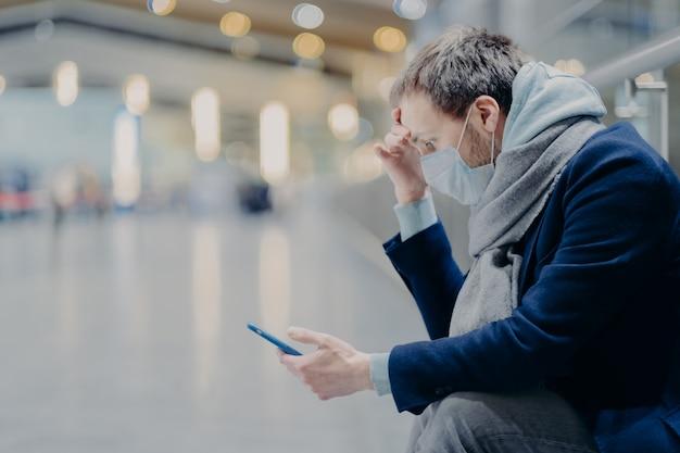 深刻な感染男性は防護マスクを着用し、コロナウイルスの流行中に健康を気にかけ、携帯電話を使用し、covid-19についてオンラインで情報を読み取り、ニュースをチェックし、屋内でポーズをとります。情報パニック