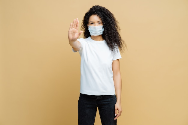 病気を広めることはありません。真剣な表情のアフロアメリカンの女性は、ストップジェスチャを行い、医療用マスクを着用し、ウイルスcovid-19を防ぎ、屋内で孤立しています。感染症をすぐに止める