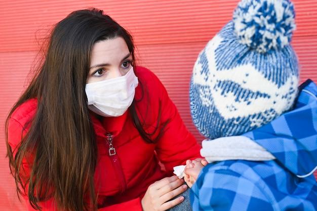 コロナウイルス、covid-19の大流行の発生時に赤ちゃんと一緒に外科用フェイスマスクを着用した若い病気の母親