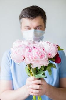 花を持って医療用マスクの若い男。アンチウイルス医療マスクの男は花束を保持しています。コロナウイルスからの回復。 covid-19のパンデミックを止める