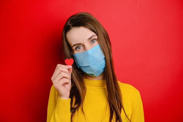 コピースペースで赤い背景に分離された小さな赤いハートを保持しているcovid-19の感染拡大を防ぐための医療用フェイスマスクを持つかわいい若い女性。流行性パンデミック拡散コロナウイルス