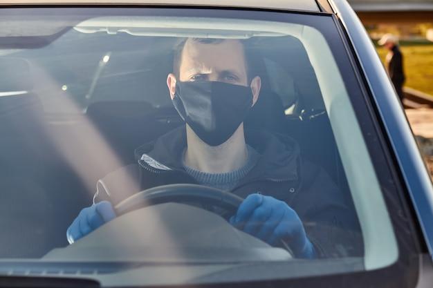 Covid-19コンセプト。男は青い保護医療用手袋と黒いマスクで車を運転します。細菌やウイルスからの保護。コロナウイルス防止。保証とコロナ病。
