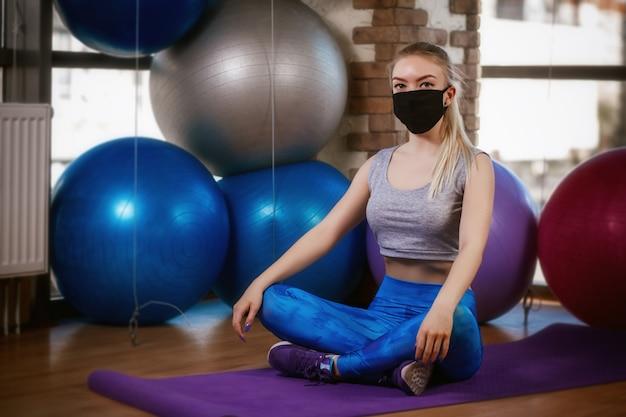 防護マスクのかわいい女の子は、敷物の蓮華座に座っています。コロナウイルス(covid-19)保護の概念。