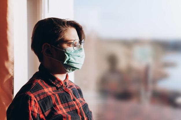 Covid-19の防護マスクをした少女が窓に立ち、自然を見つめる